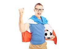 Fan masculina eufórica que sostiene un balón de fútbol y una bandera de Holanda Fotografía de archivo libre de regalías