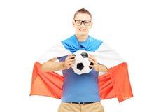 Fan masculina joven que sostiene un balón de fútbol y una bandera de Holanda Imagenes de archivo