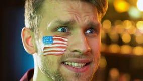 Fan masculino americano descontentado con pérdida nacional del equipo de fútbol, bandera en mejilla almacen de metraje de vídeo