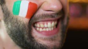 Fan masculino con la bandera italiana en mejilla que anima emocionalmente para el equipo de deporte nacional almacen de video