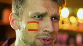 Fan masculino descontentado con pérdida nacional del equipo de fútbol, bandera española en mejilla almacen de metraje de vídeo
