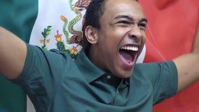 Fan mexicano que celebra mientras que sostiene la bandera de México en la cámara lenta