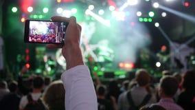 Fan mit Smartphone in Hand notiert Video auf Hintergrundmenge in den hellen Stadiumslichtern am Rockfestival stock video footage