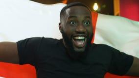 Fan negra emocionada que agita la bandera inglesa, victoria nacional del equipo de deportes que disfruta almacen de metraje de vídeo