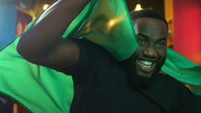 Fan negra feliz que agita la bandera brasileña, victoria nacional del equipo de deportes que disfruta almacen de metraje de vídeo