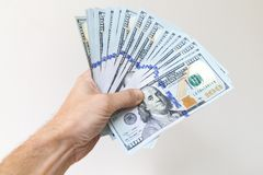 Fan of One Hundred Dollars notes in male hand Royalty Free Stock Image