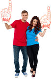We are fan of our sports club, are you?. Excite young couple showing boo hurray foam hand and cheering against white background Royalty Free Stock Image