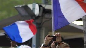 Fan patriottici che incoraggiano squadra di football americano, le bandiere d'ondeggiamento e filmanti partita sul telefono archivi video