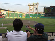 Fan photographs baseball game with digital camera Royalty Free Stock Image