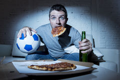 Fan piłki nożnej mężczyzna dopatrywania mecz piłkarski na tv kanapy leżance z piłki nożnej pizzą w jego usta i piłką w domu Obrazy Royalty Free