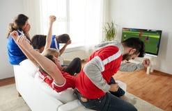 Fan piłki nożnej ogląda mecz piłkarskiego na tv w domu Zdjęcia Royalty Free