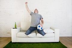 Fan piłki nożnej ogląda tv dopasowanie na kanapie z trawy smoły dywanem c Zdjęcia Stock