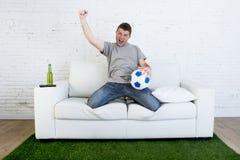 Fan piłki nożnej ogląda tv dopasowanie na kanapie z trawy smoły dywanem c Obraz Royalty Free