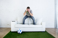 Fan piłki nożnej ogląda tv dopasowanie na kanapie z trawy smoły dywanem ja Zdjęcie Stock