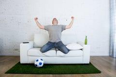 Fan piłki nożnej ogląda tv dopasowanie na kanapie z trawy smoły odświętności dywanowym celem Fotografia Royalty Free