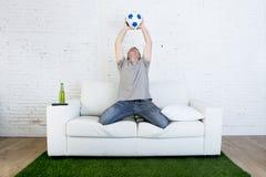 Fan piłki nożnej ogląda tv dopasowanie na kanapie z trawy smoły odświętności dywanowym celem Zdjęcia Royalty Free