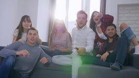 Fan piłki nożnej w backlight, działający przyjaciele skaczą na kanapie i obracają dalej TV oglądać dopasowanie i wtedy świętować zbiory wideo
