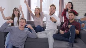 Fan przyjaciół bieg kanapa i obraca dalej TV oglądać wtedy świętować sukces z wysokością i dopasowanie pięć i z podnieceniem zbiory wideo