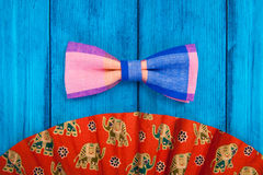 Fan with red bow tie on blue background. Fan with red bow tie on blue wooden background Stock Illustration