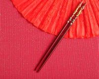 Fan rouge de main avec un ensemble de baguettes rouges Photo stock