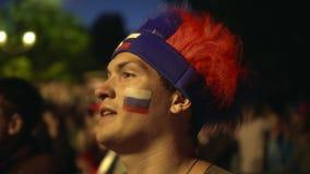 Fan ruso con la pintura en su cara que mira tenso el partido de fútbol, experimentando metrajes