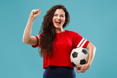 Fan sport woman player holding soccer ball isolated on blue background. Fan sport woman player holding soccer ball isolated on blue studio background. Human stock images