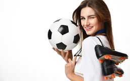 Fan sport woman player in red uniform hold soccer ball and boots celebrating winking on white. Background stock image