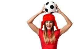 Fan sport woman player in red uniform and russian winter hat hold soccer ball celebrating. Fan sport woman player in red uniform hold soccer ball on head royalty free stock image