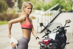 Fan of sports and fast engines. Beauty blonde sport woman. Close up royalty free stock images
