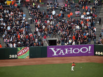 Fan stretches for a homerun ball, fielder watches Stock Images