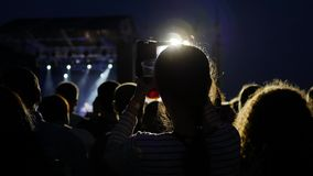 Fan take mobile foto, people shoots video using phone on concert, fans at live music concert stock video footage