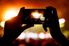 Fan taking photo of concert at festival by smatphone. Arched stage on screen Stock Photography