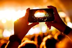 Fan taking photo of concert at festival by smatphone. Arched stage on screen Royalty Free Stock Image