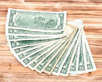 Fan of two dollar bills. On vintage wooden background royalty free stock photos