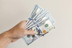 Fan von 100 Dollar Anmerkungen in der männlichen Hand Stockfotografie