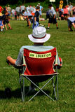 Fan watching football game. Spectator sitting in folding chair watching childrens sports game Stock Photography