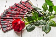 Fan y rosa plegables del rojo foto de archivo