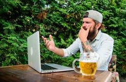 Fan zegarka strumień online podczas gdy siedzi taras outdoors z piwnym kubkiem Brutalny mężczyzna czas wolny z piwem i sport grze fotografia royalty free