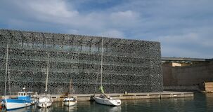 Marseille, Bouches du Rhone, France. The Fanal tower fort Saint Jean and the modern facade of Mucem. In the forground is the J4 bassin stock video