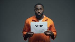Fanale di arresto afroamericano della tenuta del prigioniero, discriminazione razziale, persecuzione video d archivio