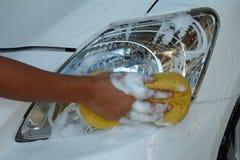 Fanali anteriori di lucidatura della mano della femmina dell'automobile dalla spugna e dal sapone Fotografia Stock Libera da Diritti