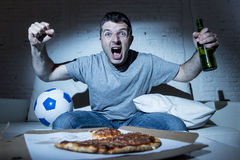 Fanatic crazy football fan watching television soccer screaming happy celebrating scoring goal Royalty Free Stock Photography