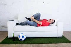 Fanatic football fan lying on couch sofa with ball on green grass carpet emulating soccer stadium pitch mocking player in pain hur Stock Images
