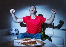 Fanatic football fan man watching soccer game on tv celebrating Royalty Free Stock Image