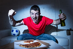 Fanatic football fan man watching soccer game on tv celebrating Royalty Free Stock Photo