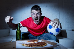 Fanatic football fan man watching soccer game on tv celebrating Royalty Free Stock Images
