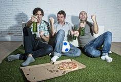 Fanatieke ventilatorsvrienden die op voetbal op TV-het vieren doelsc letten Royalty-vrije Stock Foto's