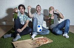 Fanatieke ventilatorsvrienden die op voetbal op TV-het vieren doelsc letten Stock Fotografie