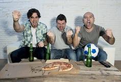 Fanatische Fußballfane der Freunde, die Spiel im Fernsehen feiert schreiendes verrücktes glückliches des Ziels aufpassen Lizenzfreies Stockbild