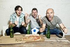 Fanatische Fußballfane der Freunde, die Spiel im Fernsehen feiert schreiendes verrücktes glückliches des Ziels aufpassen stockbild